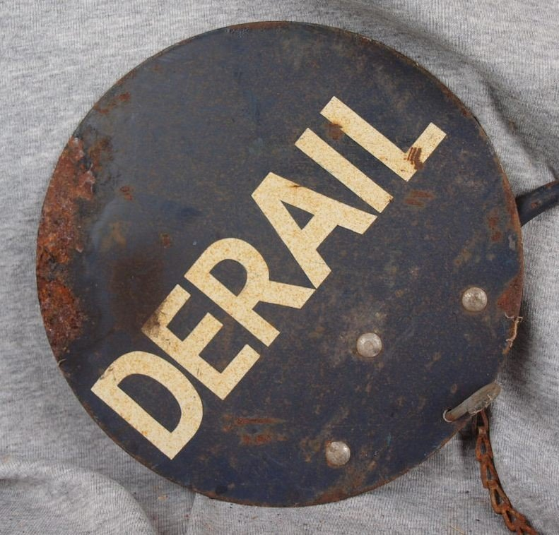"""223:  Metal sign on arm """"DERAIL"""", 2 sided, rust"""
