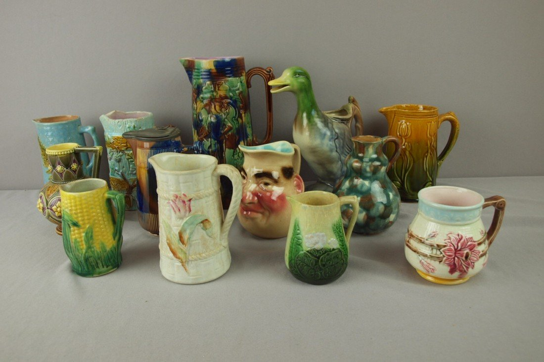 239: Majolica lot of 13 pitchers, various condition