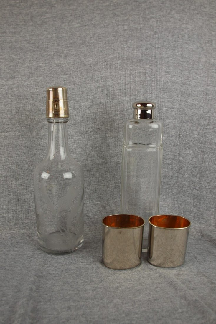 613:  Lot of 2 glass liquor bottles, one with sterling