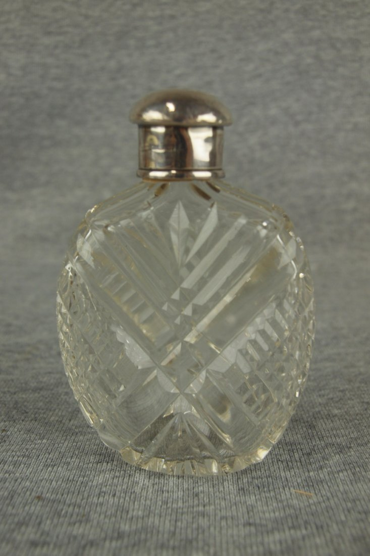 Cut glass whiskey flask with silver top, circa 1910