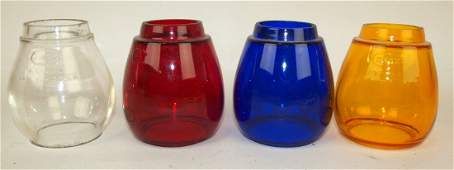 Four Dietz railroad lantern globes: clear, cobalt, red,