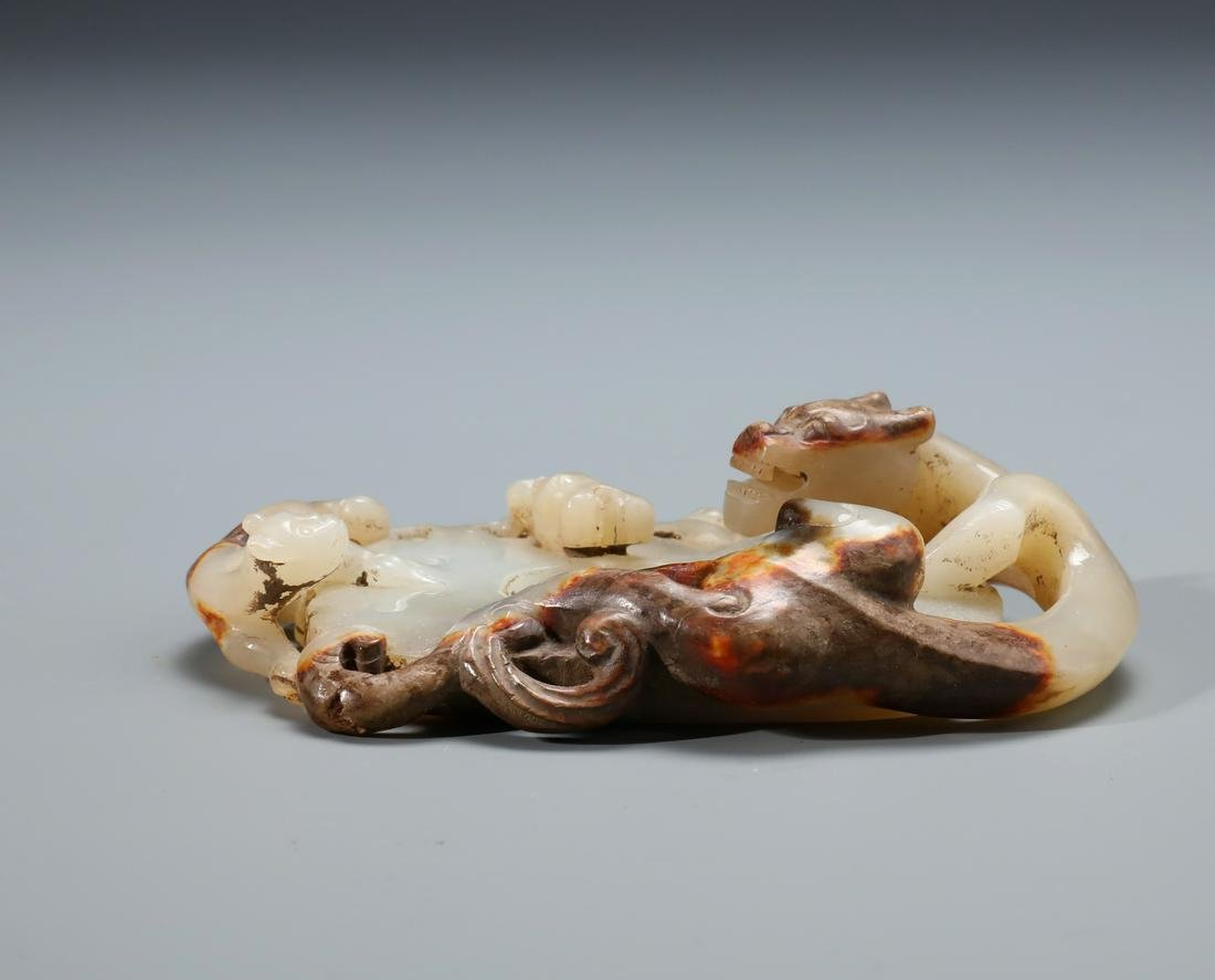 A Finely Carved Chinese White and Russet Jade Chilong