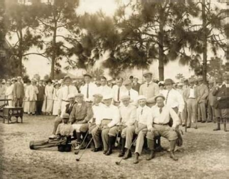 1018: A sepia group photograph of golfers with caddie