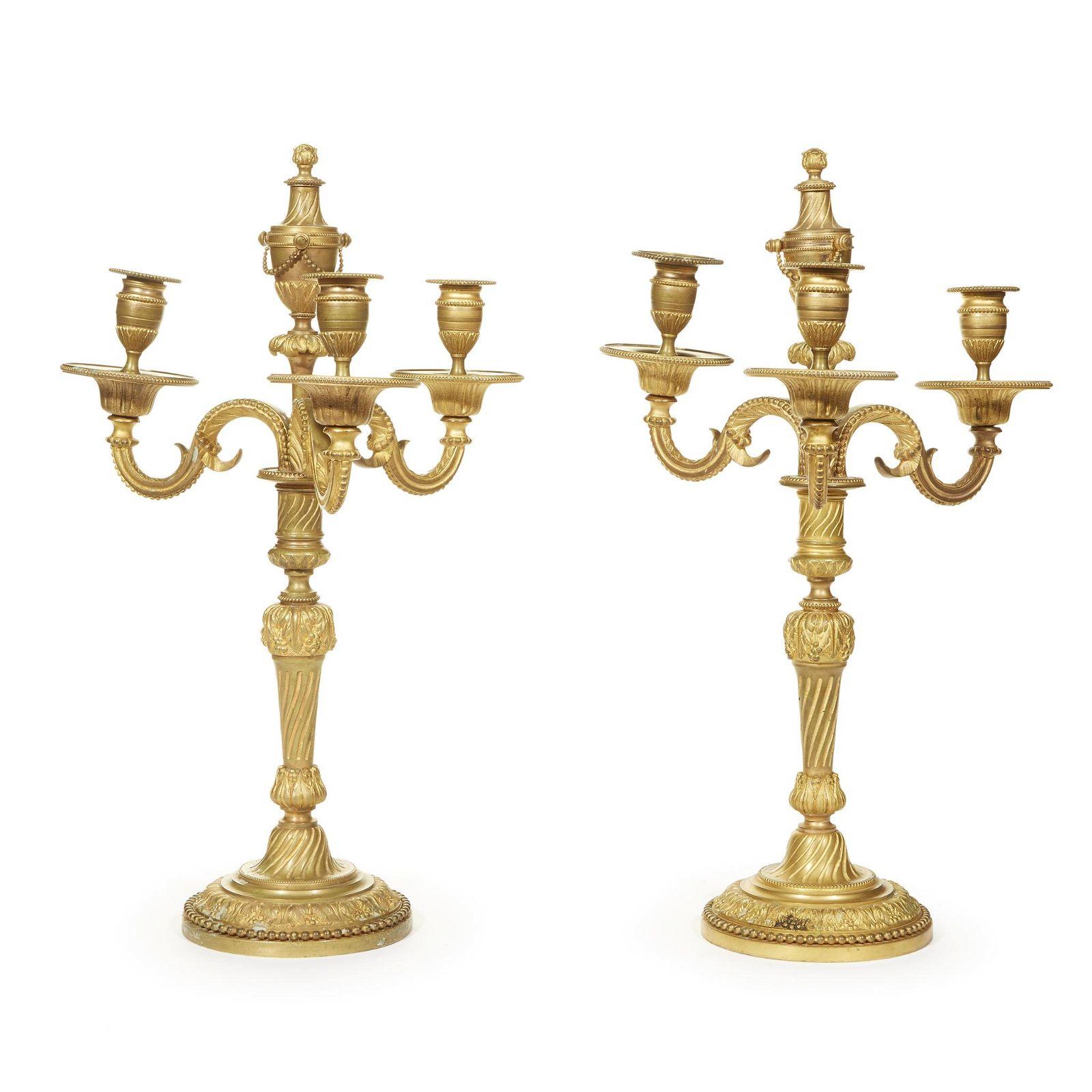 A pair of Louis XVI style gilt-bronze three-light