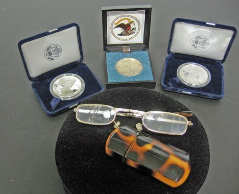 3: Three Silver Dollar Coins and Reading Glasses in Cas