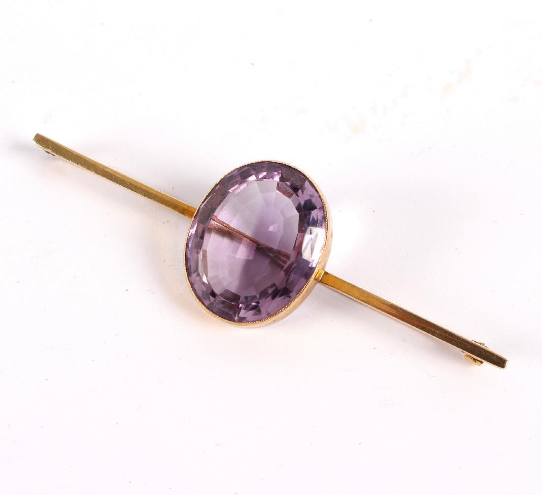 An amethyst bar brooch, the large oval stone