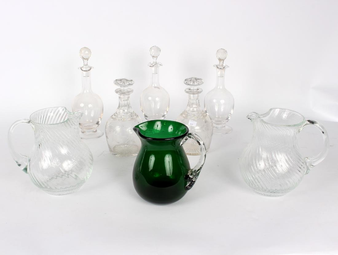 A group of glass decanters and jugs comprising a cut