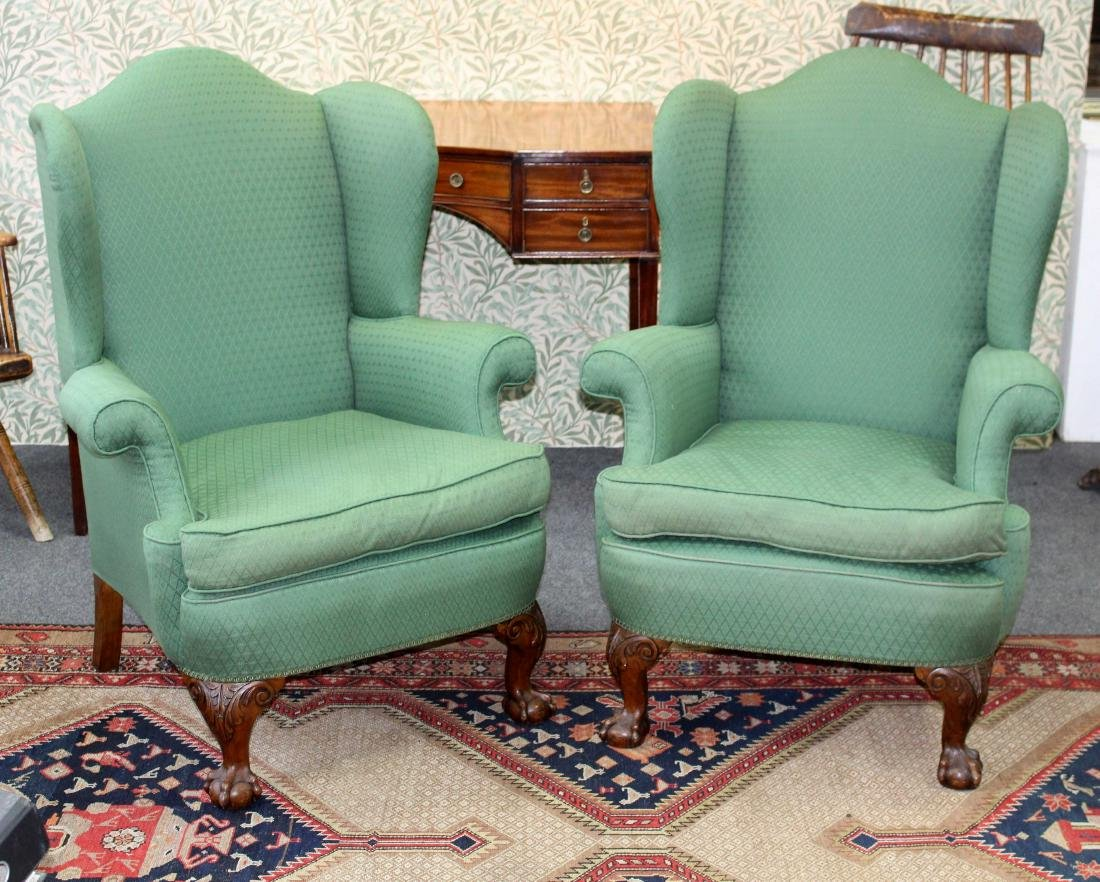 A pair of wing back upholstered armchairs, on carved