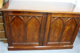 A mahogany cupboard enclosed by a pair of twin arch