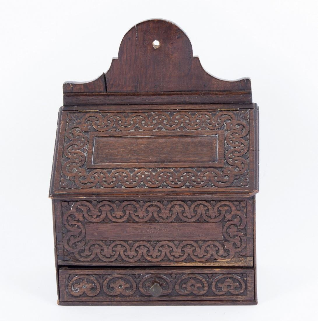 An oak candle box with carved front, hinged cover and