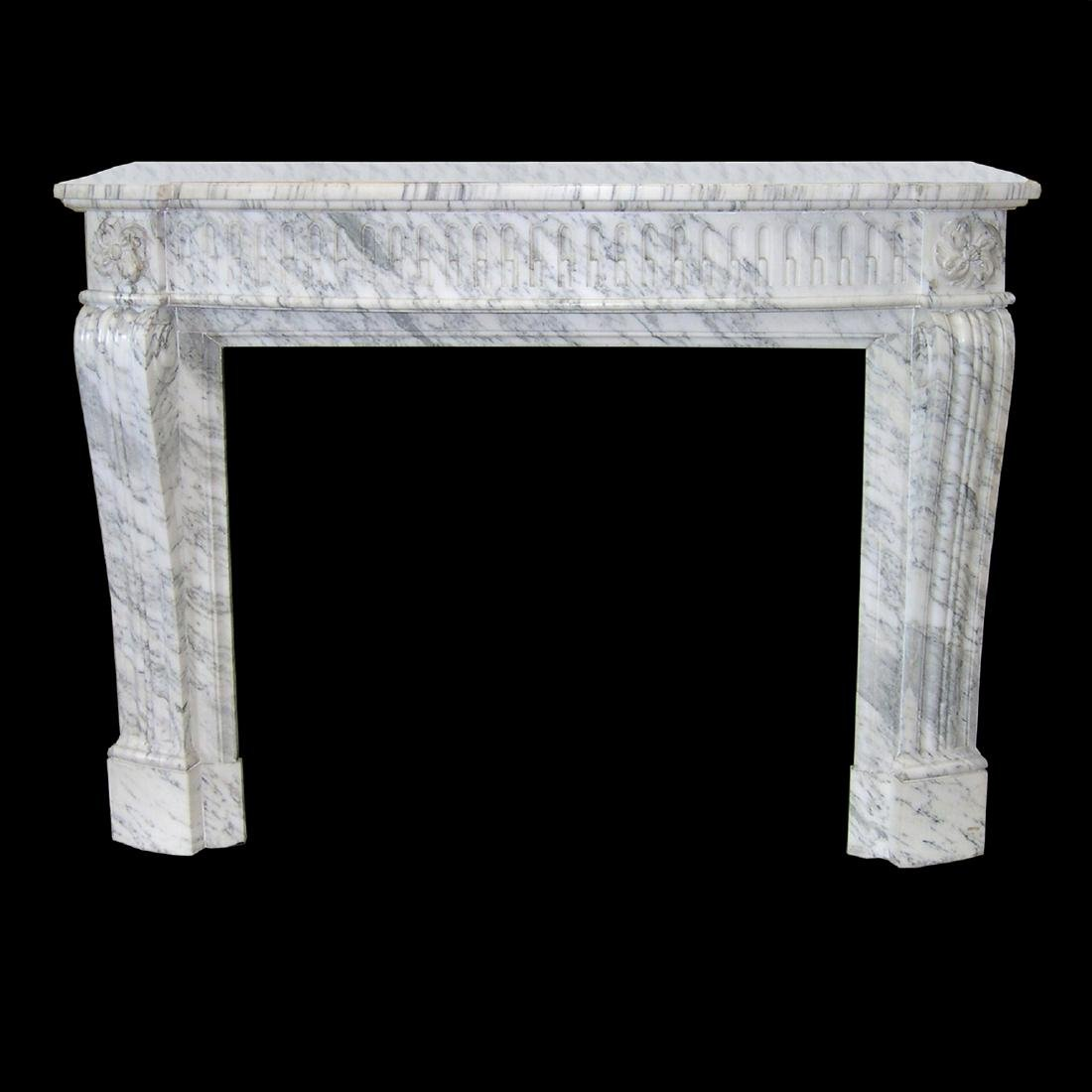A carved Louis XVI style chimney piece in Arabascato