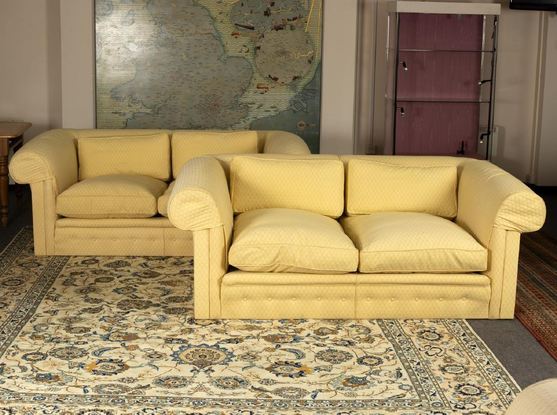 A pair of upholstered two-seater sofas with buttoned