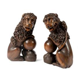 A pair of Renaissance style carved oak seated lions,