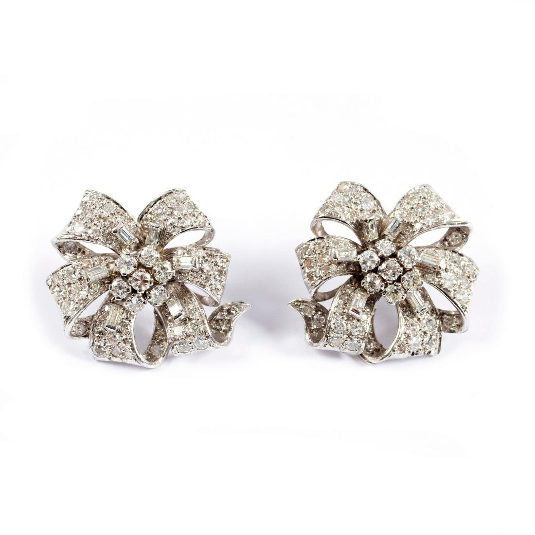A pair of diamond ear studs, each of ribbon tie form