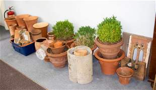 A large quantity of terracotta planters and stands and
