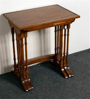 A nest of three mahogany tables on turned supports with