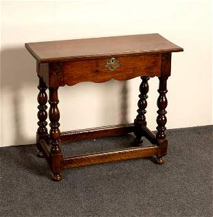 An oak table with shaped frieze on baluster turned