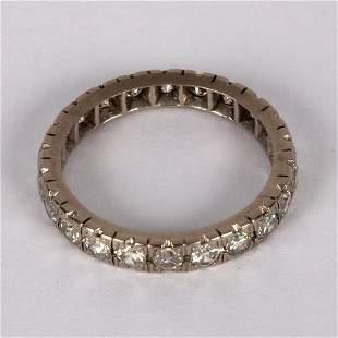A diamond eternity ring set in white precious metal,