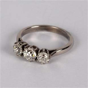 A diamond three-stone ring, claw set in precious white