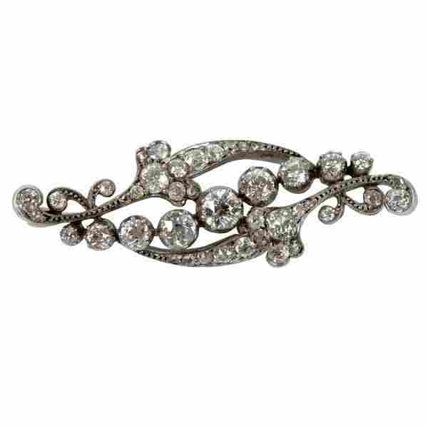 A diamond brooch of scrolling form, the central line of