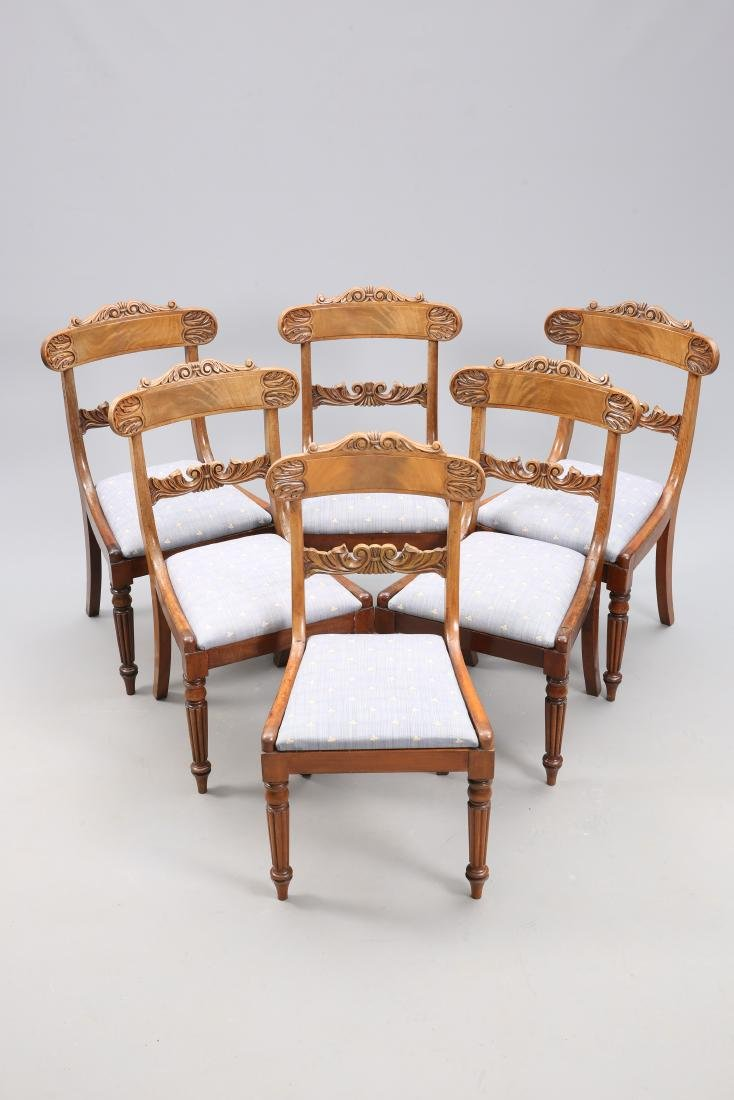 A SET OF SIX REGENCY MAHOGANY DINING CHAIRS, each crest