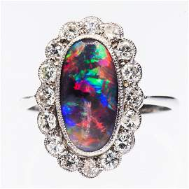 A PLATINUM, BLACK OPAL AND DIAMOND RING, the oval cut