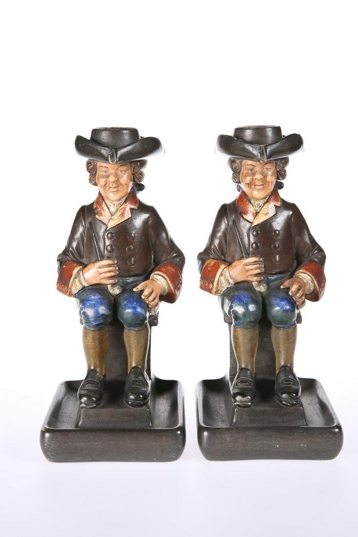 A PAIR OF CONTINENTAL POTTERY TOBY CHAMBERSTICKS, LATE