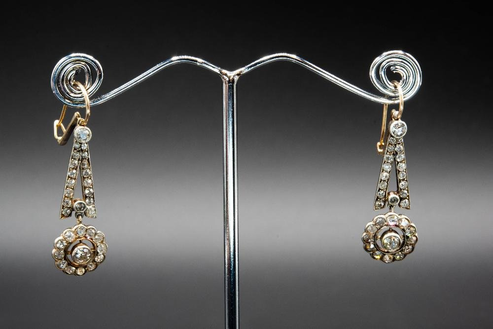 A PAIR OF DIAMOND SET EARRINGS, with flower head mount