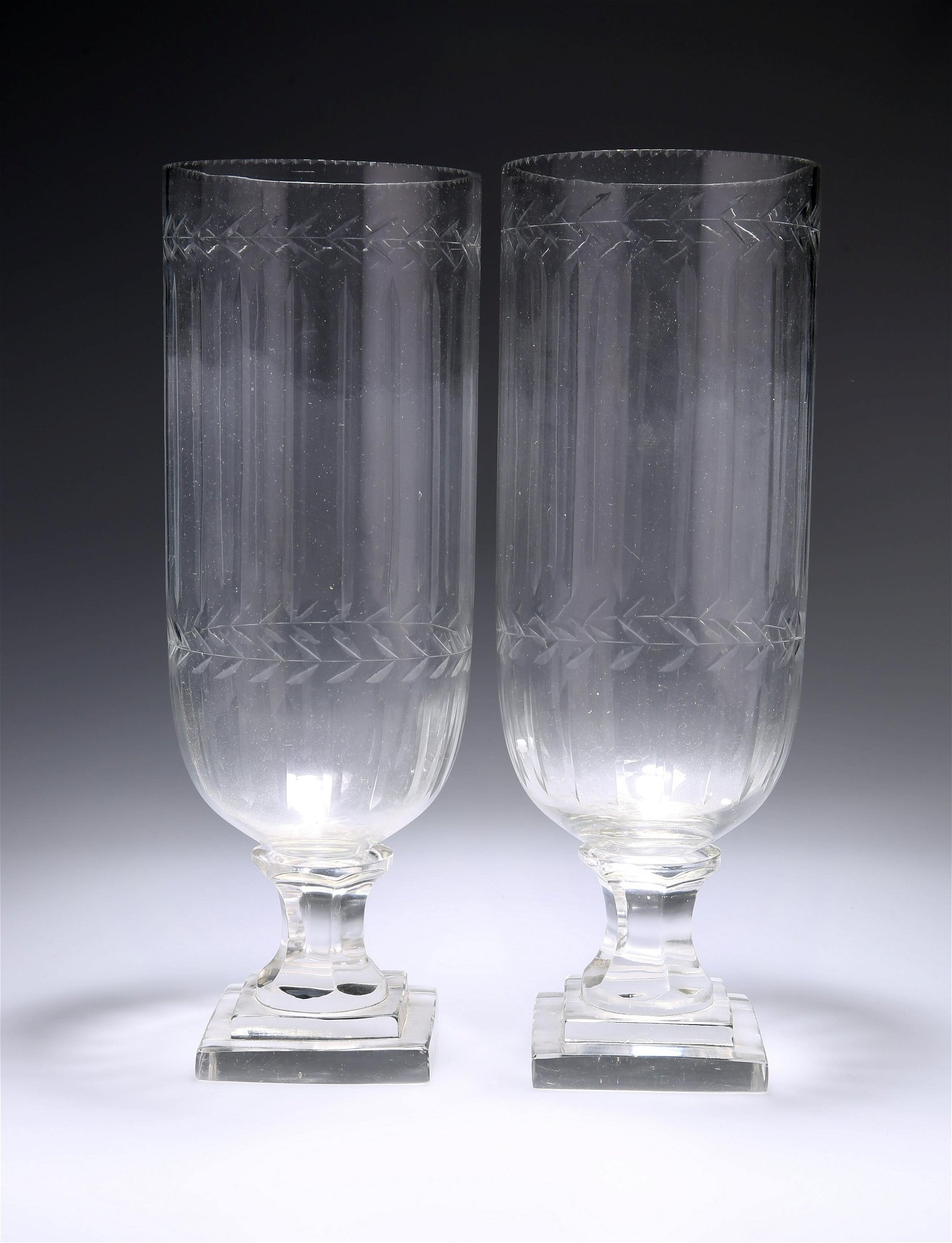 A PAIR OF CUT-GLASS VASES, each raised on stepped