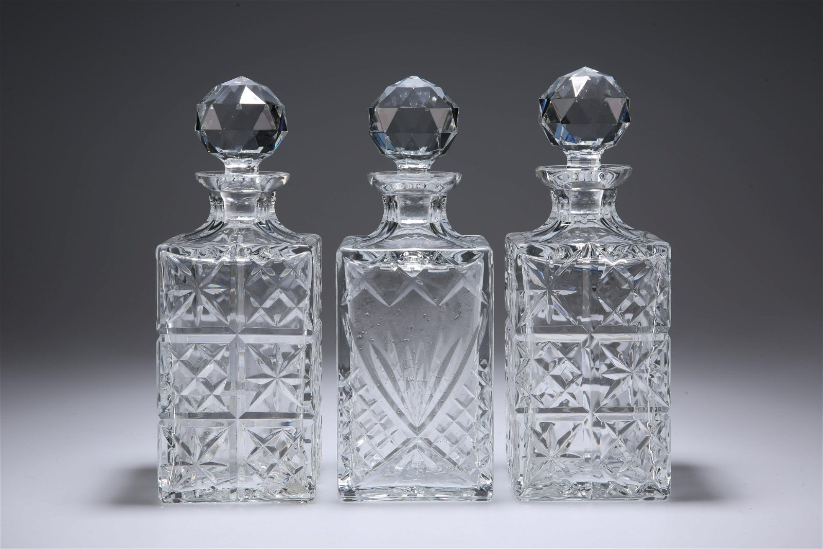 THREE LARGE SQUARE-SECTION GLASS DECANTERS. 26.5cm high