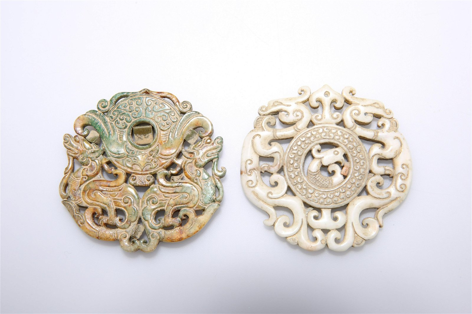 TWO CHINESE JADE PENDANTS, each pierced and carved.