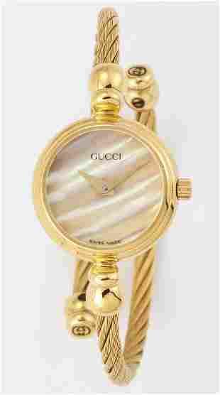 A LADY'S GOLD PLATED GUCCI BANGLE WATCH,circular