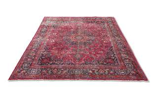 A LARGE PERSIAN MASHAD CARPET, the red ground with