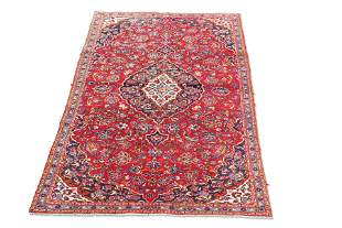 A PERSIAN KASHAN CARPET, with red ground. 268cm by