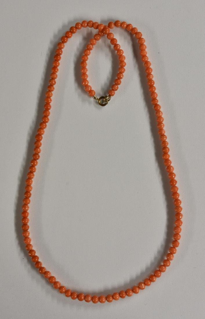 A polished globular coral bead single strand necklace,