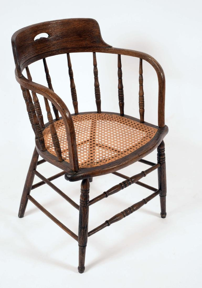 A late 19th century oak desk chair, curved spindle back