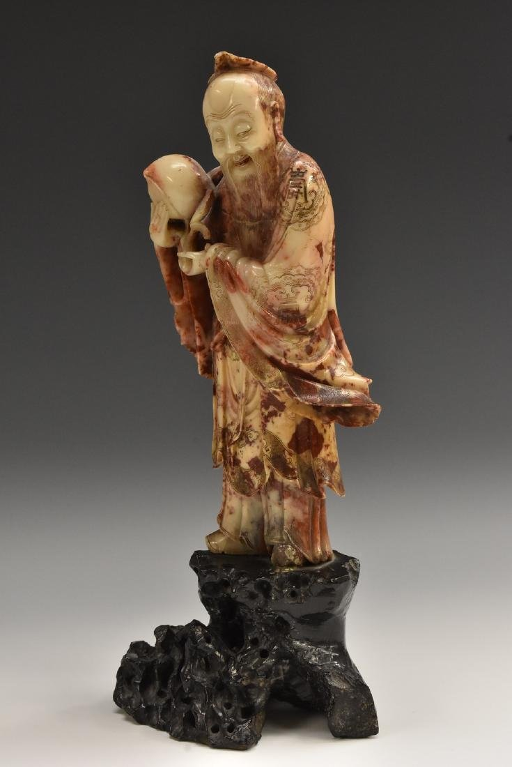 A Chinese soapstone figure, carved as an immortal