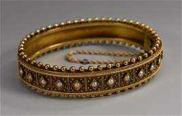 A Victorian Etruscan Revival hinged bangle set with a