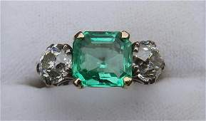 An art deco three stone emerald & diamond ring, the