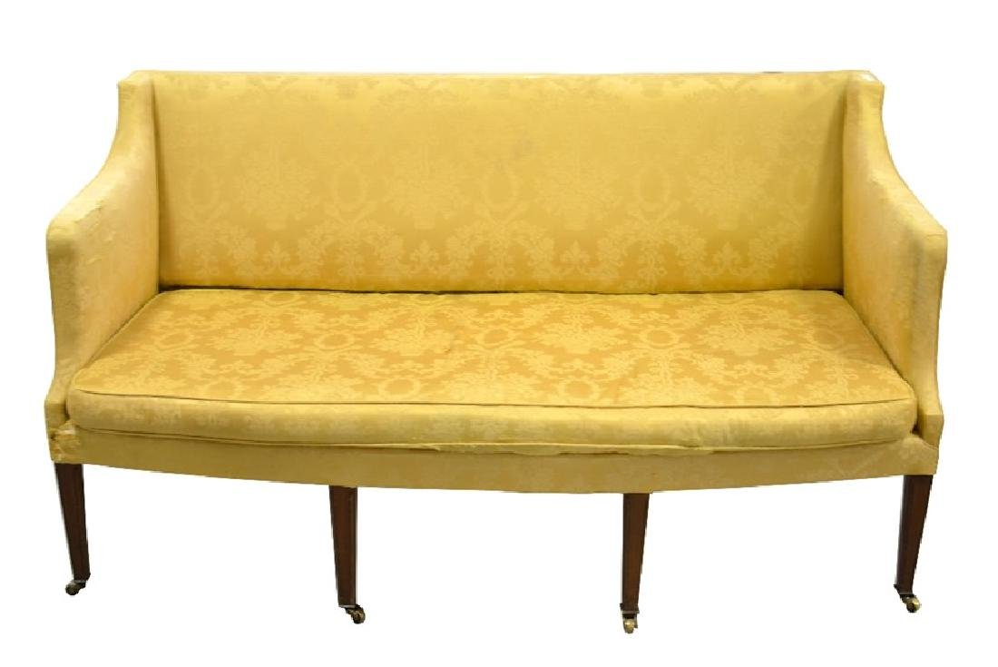 An Edwardian three seater sofa, bow fronted on four