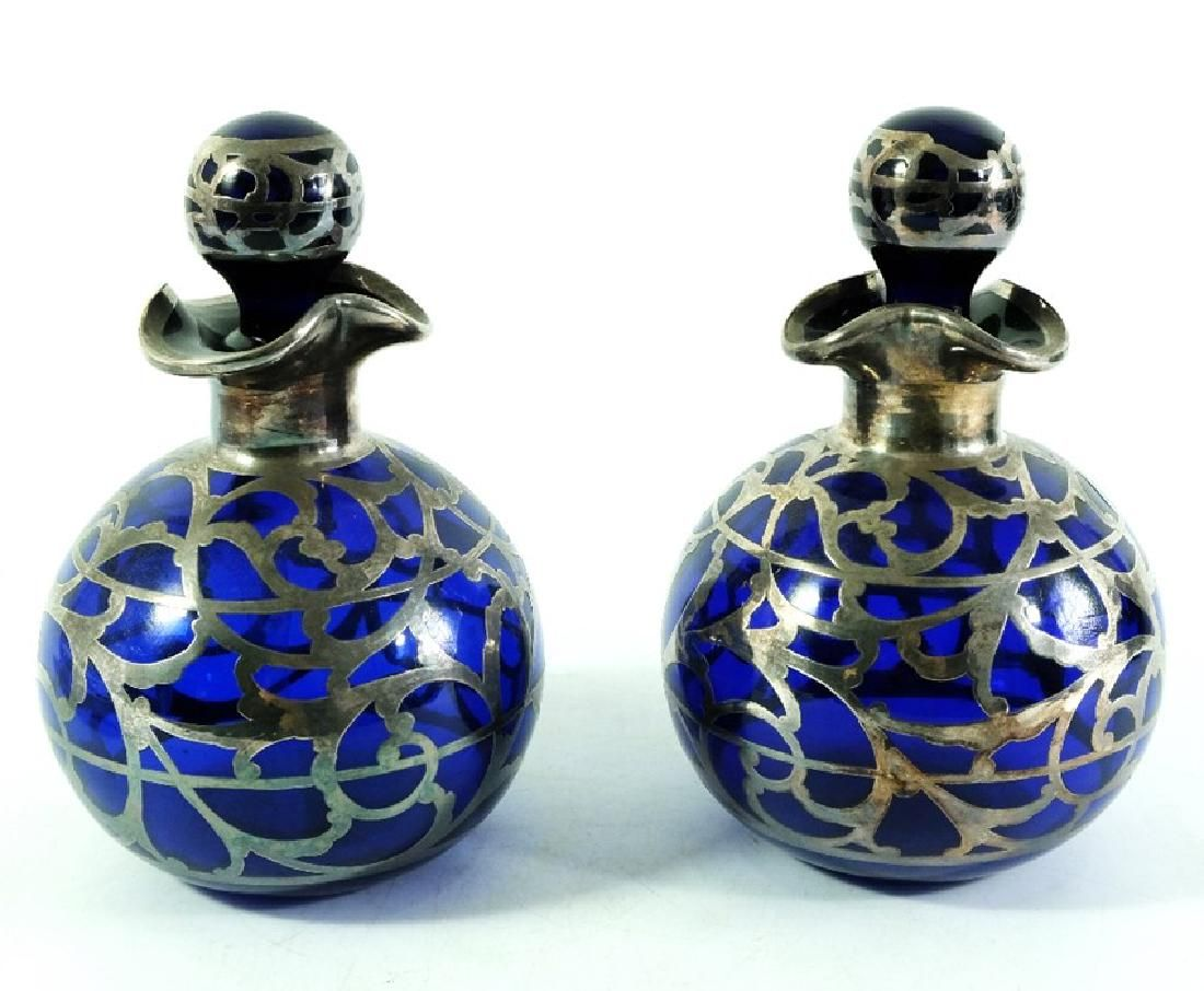 A pair of silver overlay blue glass scent bottles,