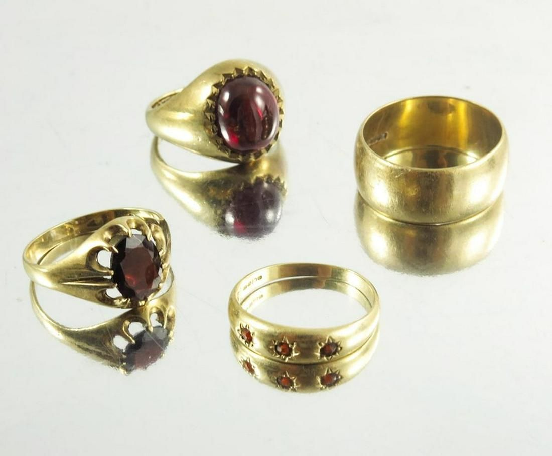 A collection of 9 carat gold rings, including garnet