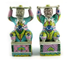 A pair of Chinese polychrome figures with raised arms