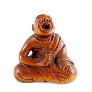 A Japanese carved wood netsuke Meiji modelled as a