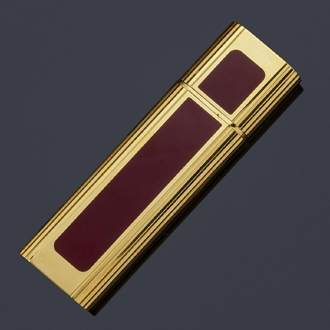 Cartier golden perfume bottle with maroon lacquer.