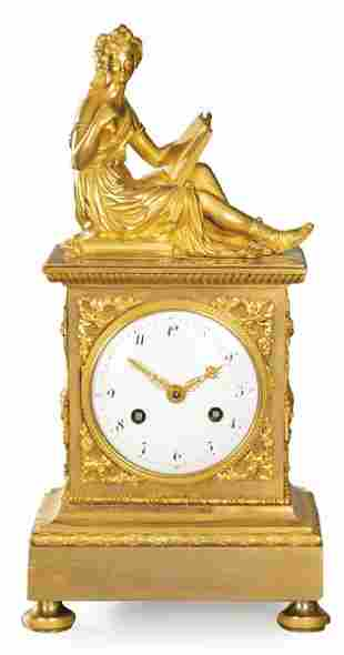 Empire table clock in gilt bronze. On a high base,