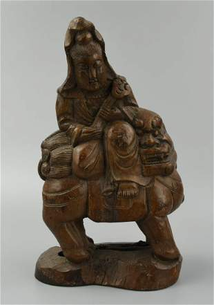 A Wood Carving of Guanyin Upon a Buddhist Lion