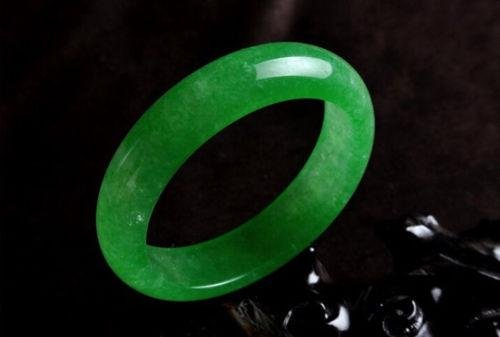 A NATURAL GREEN JADE BANGLE.