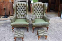 Pair of green leather wing back arm chairs.
