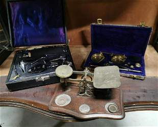Two brass scales and a cased medical set.